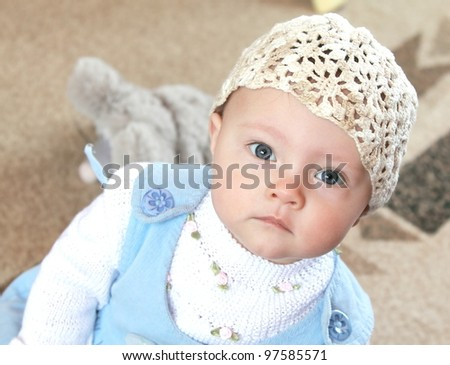 Serious baby in funny hat and blue dress sitting and looking in camera - stock photo
