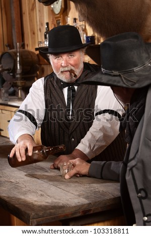 Serious bartender with cigar pours drink for customer - stock photo