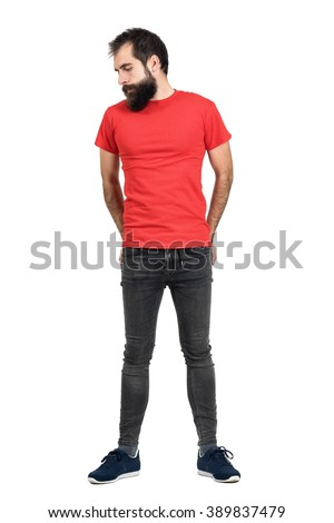 Serious bearded hipster in red t-shirt with hands in his back pocket looking down. Full body length portrait isolated over white studio background. - stock photo