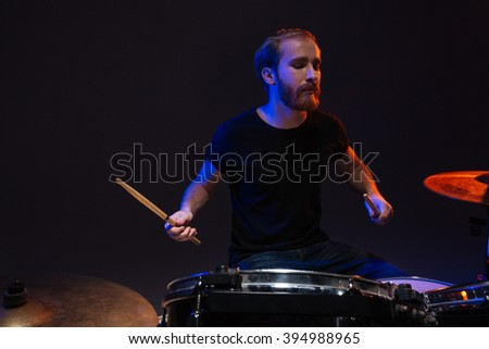 Serious bearded male drummer playing drums over dark background