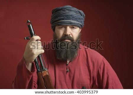 Serious bearded man in a red shirt  and turban with arms looking forward on a red background