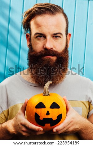 Serious bearded man showing a Jack O'Lantern pumpkin. - stock photo