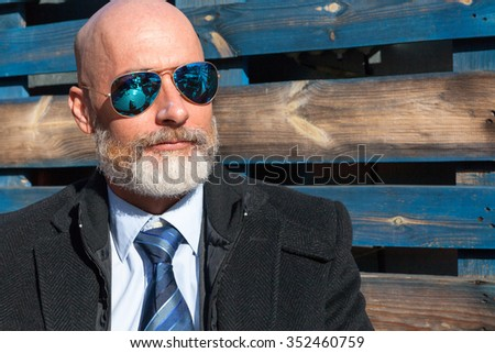 Serious bearded  middle-aged man with blue reflective sunglasses - stock photo