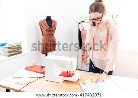 Serious beautiful young woman seamstress working and talking on mobile phone - stock photo