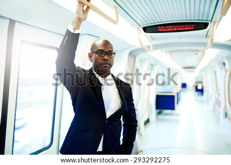 Serious Black American Businessman Commuting on a Subway Train and Holding on an Overhead Railing - stock photo