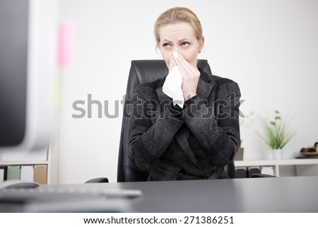 Serious Blond Businesswoman in Black Suit Blowing her Nose While Sitting at her Office and Looking Afar. - stock photo