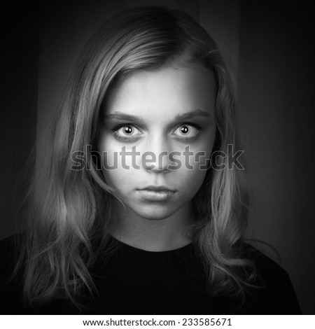 Serious blond Caucasian girl with mysterious hypnotic look - stock photo