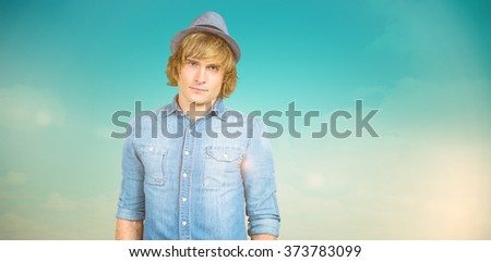 Serious blond hipster staring at camera against blue green background