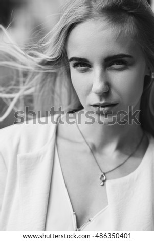 serious blond woman looking at camera, monochrome