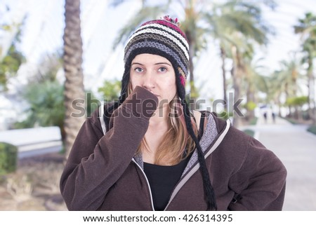 Serious blonde girl wearing multicolor bonnet