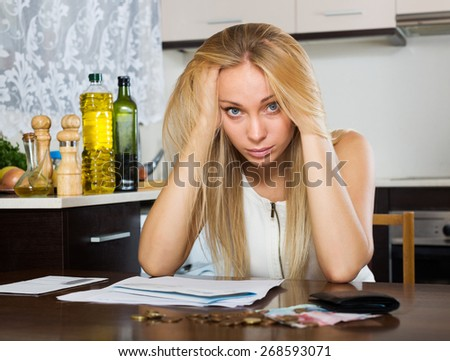 serious blonde girl with money and documents in home kitchen - stock photo