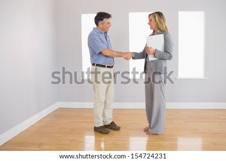 Serious blonde realtor shaking the hand of her mature buyer in an empty room - stock photo