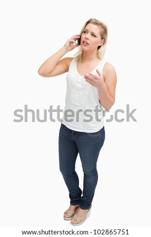 Serious blonde woman having a conversation on the phone against a white background - stock photo