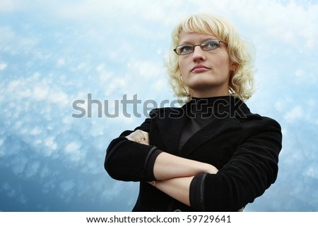 Serious blonde young woman in glasses on blue sky background - stock photo