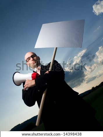Serious bold man in glasses and black suit, holding sign and megaphone. Space for text is available. - stock photo