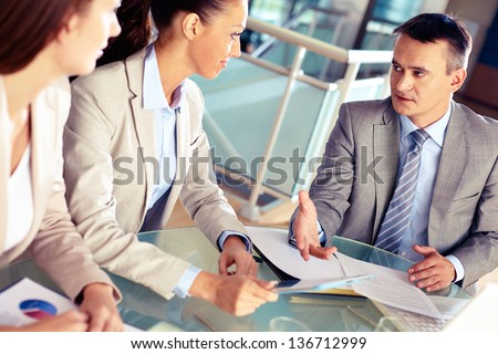 Serious boss looking at his employees while commenting a document at meeting - stock photo