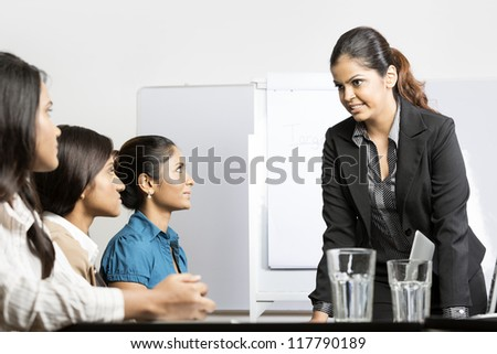 Serious boss talking with her team during a meeting. Indian business woman. - stock photo