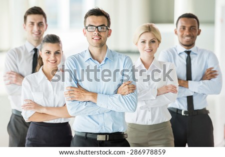 Serious boss with arms folded standing in a modern office with colleagues - stock photo