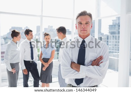 Serious boss with arms folded standing in a modern office with colleagues behind - stock photo