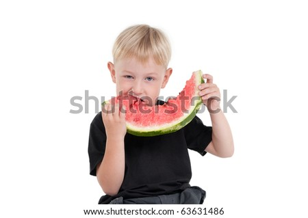 Serious boy eating a slice of watermelon - stock photo