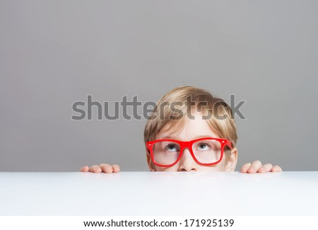 Serious boy in red-framed eyeglasses looking up from behind the table, close-up shot