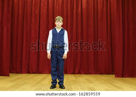 Serious boy in suit with vest stands on stage with red curtains. - stock photo