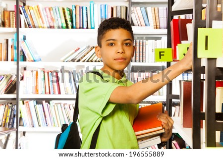 Serious boy looks and searches book on shelf - stock photo