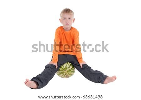 Serious boy sitting on a watermelon - stock photo
