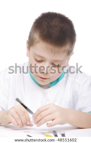 Serious boy with magnifier and tweezers closeup photo - stock photo