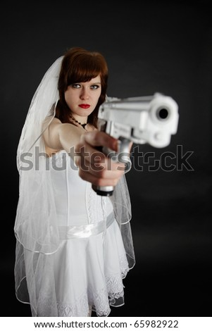 Serious bride take aim with a big pistol on blaсk background - stock photo