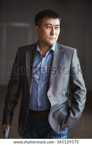 Serious brutal Asian business man with a phone in his hands, courageous portrait in a suit, looking like an action movie hero. The color in the gray tones. The rate of reaction, response, ready to go. - stock photo