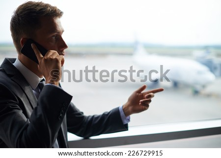 Serious business agent talking on cellular phone - stock photo
