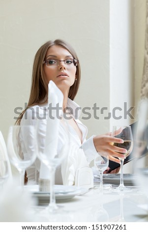 Serious business lady posing in restaurant - stock photo