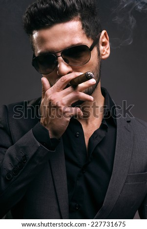 Serious business man is smoking his cigar gray background - stock photo
