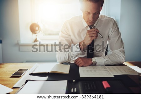 Serious business man working on documents looking concentrated with briefcase and phone on the table - stock photo