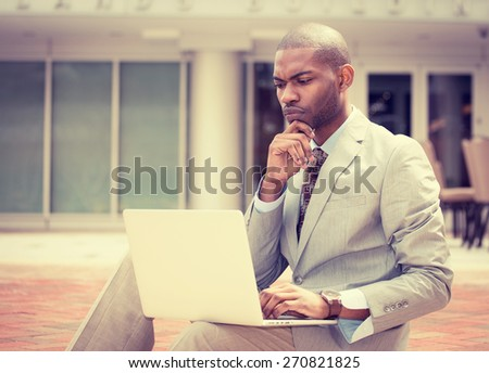 Serious business man working on laptop computer outdoors  - stock photo