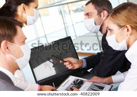 Serious business partners in protective mask looking at screen of laptop in working environment