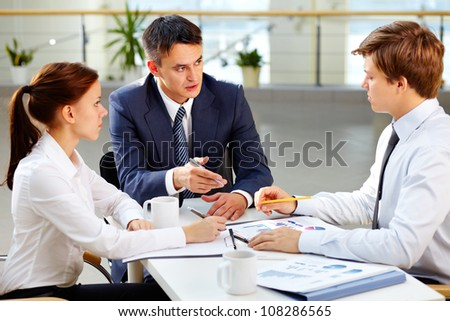 Serious business people giving a report about current results to their chief - stock photo
