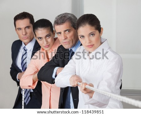 Serious business people team playing tug of war in the office - stock photo