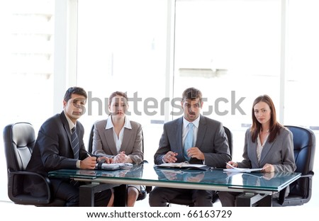 Serious business team sitting around a table during a meeting