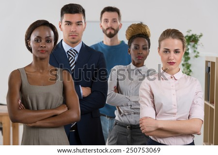 Serious business team standing together at office - stock photo