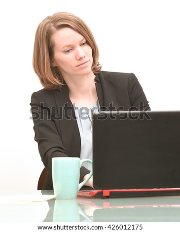 Serious business woman deep in thought while working at a computer with coffee - stock photo