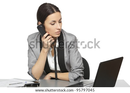 Serious business woman looking at laptop screen while talking on the phone at her work desk, isolated on white background