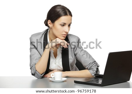 Serious business woman reading at laptop screen sitting at her work desk, isolated on white background - stock photo