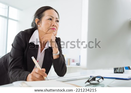 Serious business woman reading information on the screen - stock photo