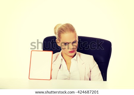 Serious business woman sitting behind the desk and holding board with ban - stock photo