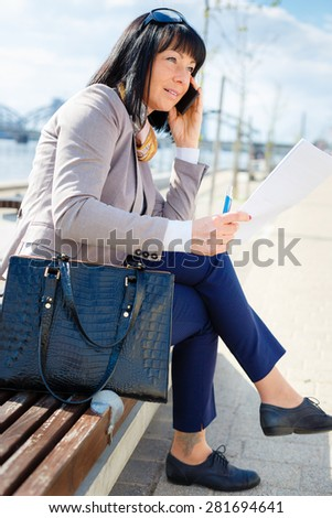 Serious business woman talking by mobile phone and read contract sitting on a park bench, focused on the job, spring mood - stock photo