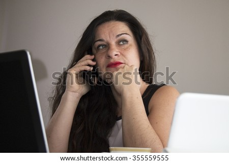 Serious business woman talking on her phone at home office