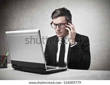 Serious businessman calling someone with a mobile phone while is using a laptop - stock photo