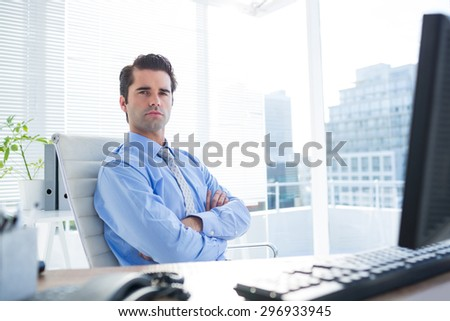 Serious businessman crosses his arms on his office - stock photo